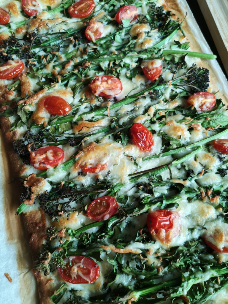 Pizza topped with sprouting broccoli
